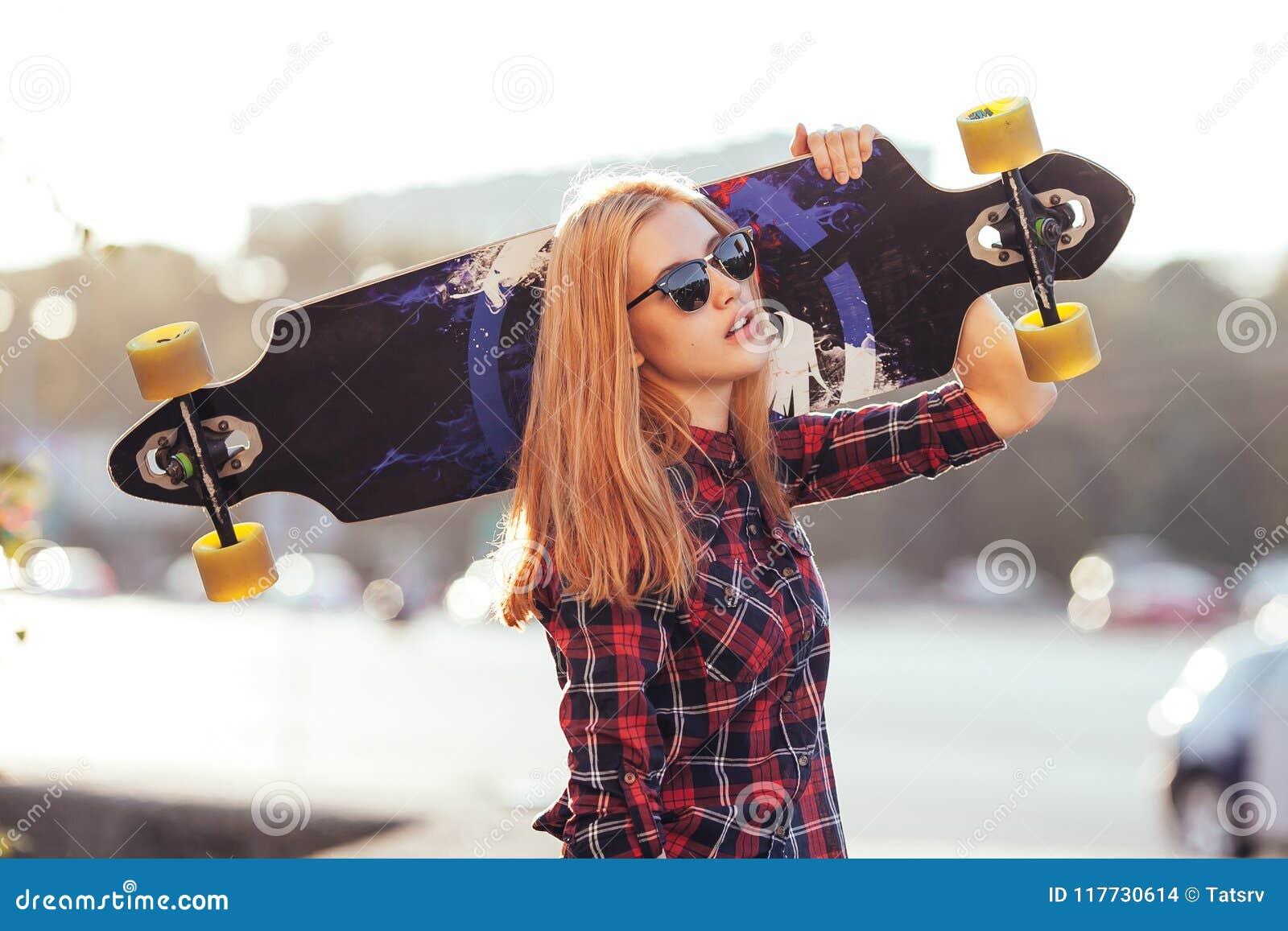 Mulher Nova Do Moderno Que Guarda O Skate Atrás Da Cabeça No Por Do ... 64d1a9289c9