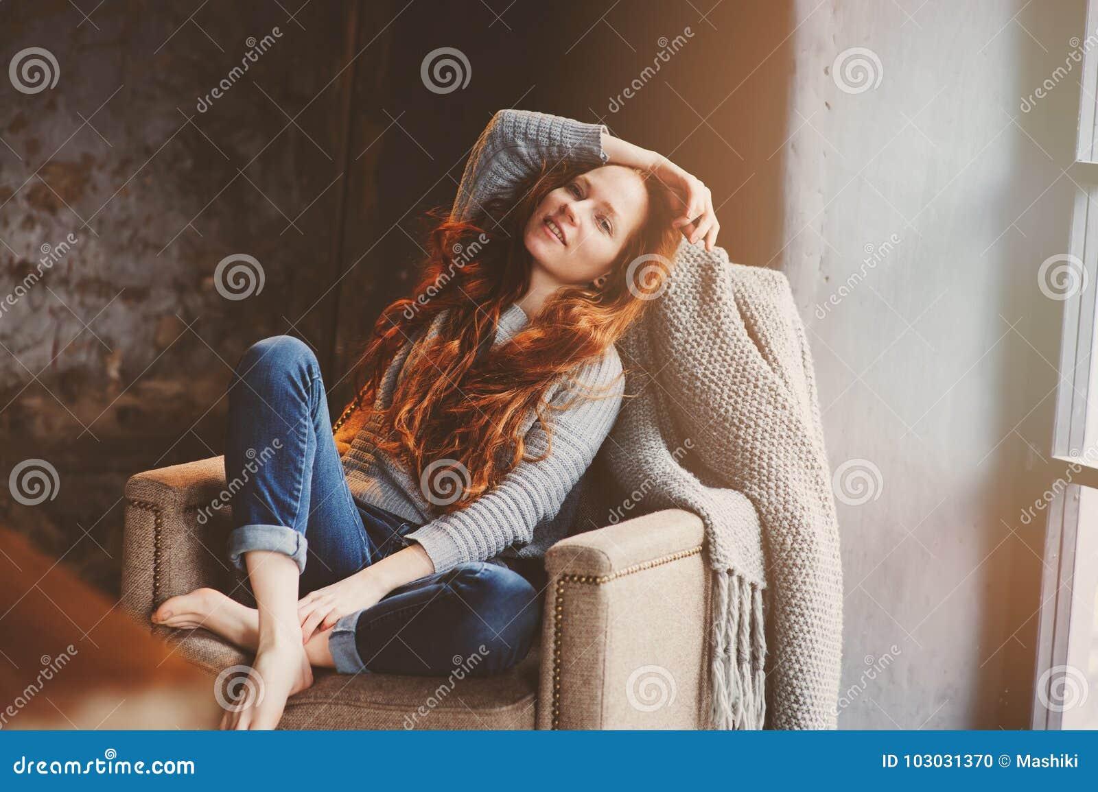 Mulher nova do readhead que relaxa em casa na cadeira acolhedor, vestida na camiseta e em calças de brim ocasionais