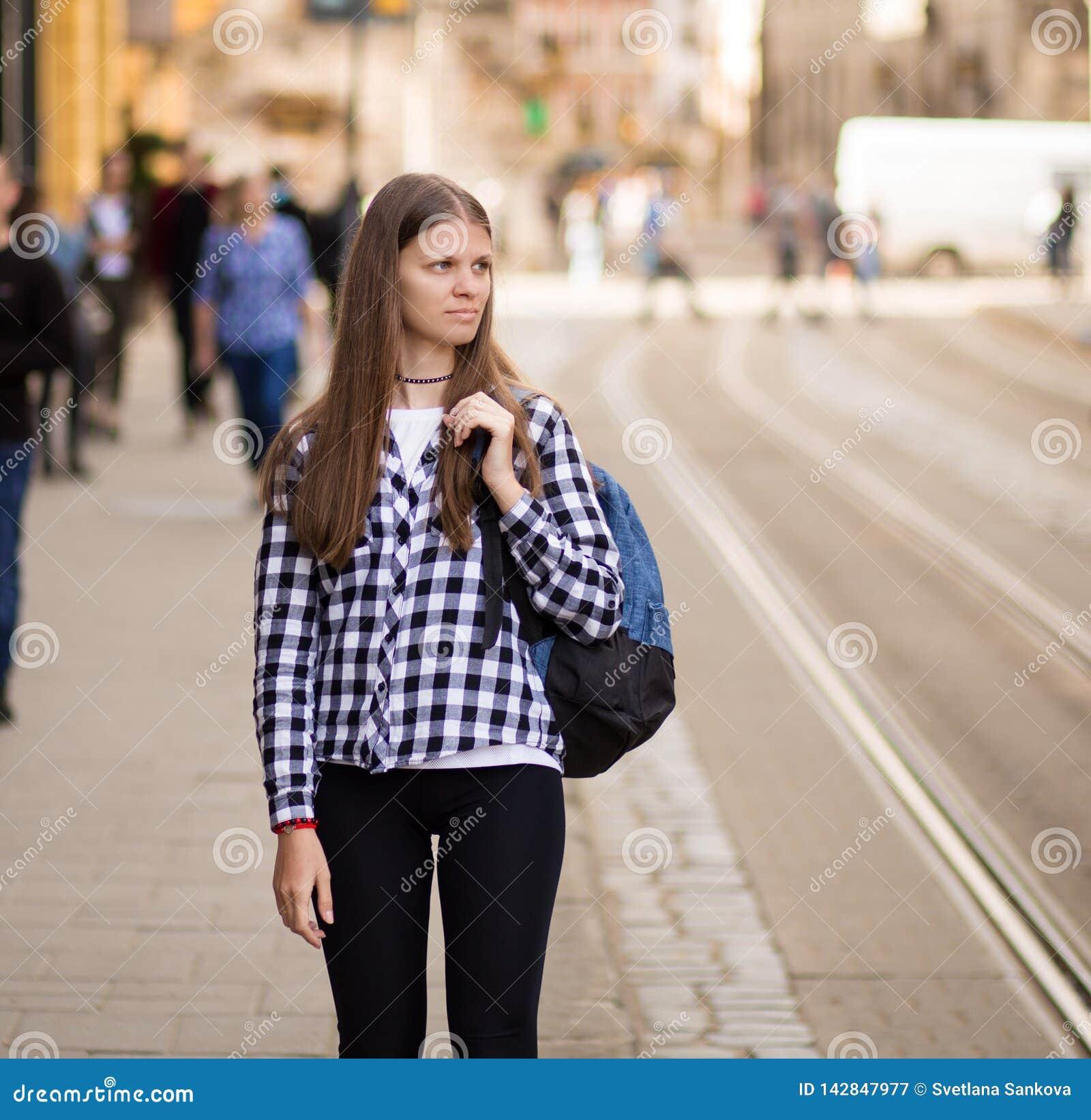 Mulher nova do turista com caminhada da trouxa pela rua na cidade velha de Europa, estilo da forma do verão