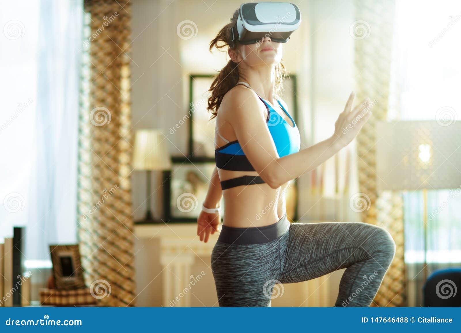 Mulher nova dos esportes na sala de visitas moderna no exerc?cio dos vidros de VR