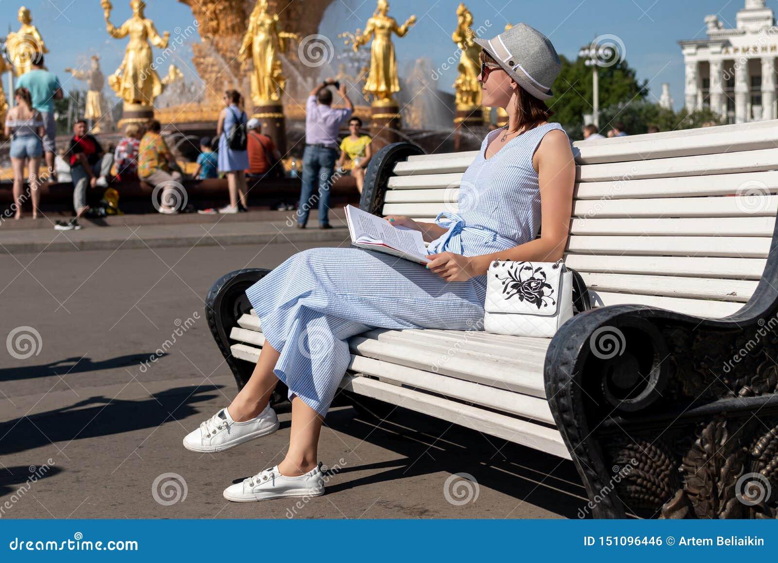 Mulher nova e à moda feliz com o chapéu e o livro que sentam-se no banco no parque
