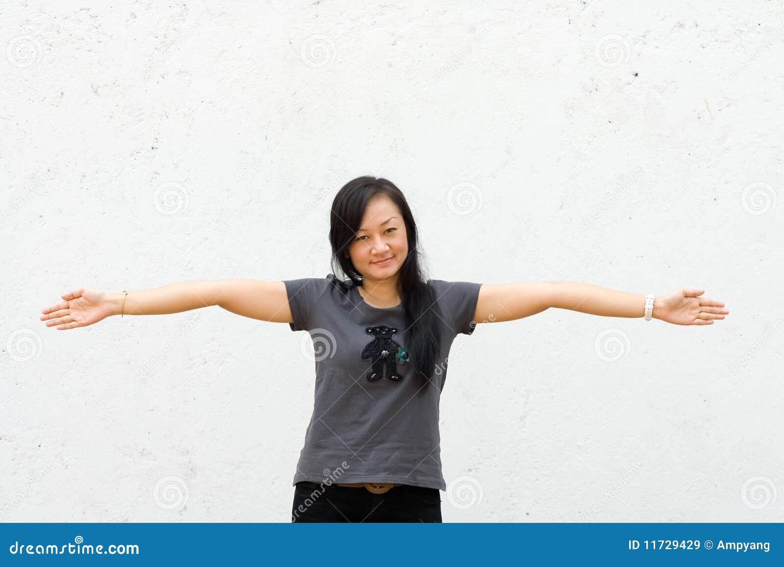 A mulher nova espalhou seus braços largamente abertos