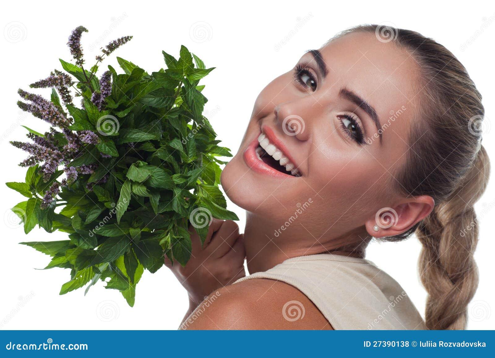 Mulher nova feliz com com um pacote de hortelã fresca