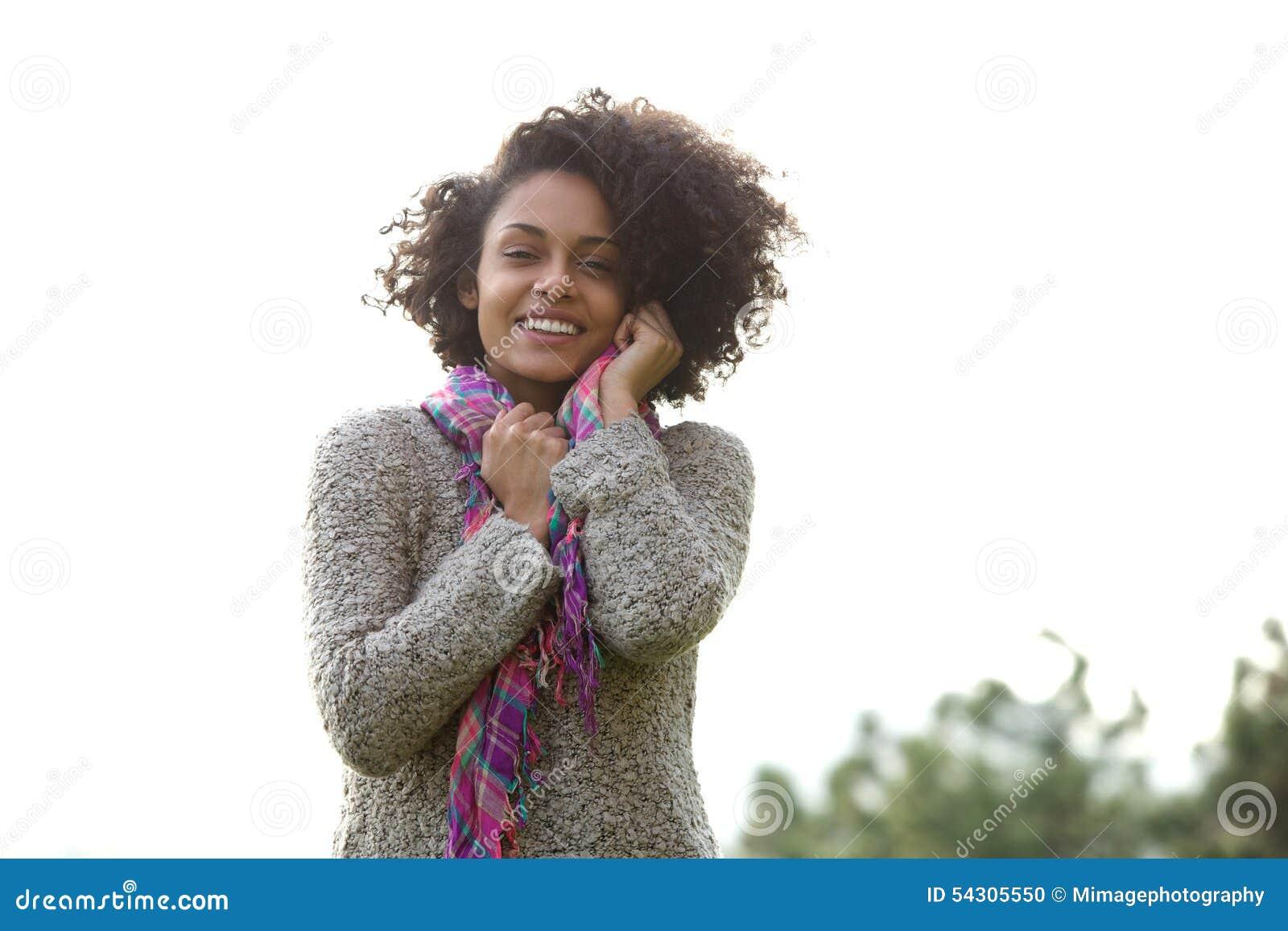 Mulher nova feliz da raça misturada que sorri fora