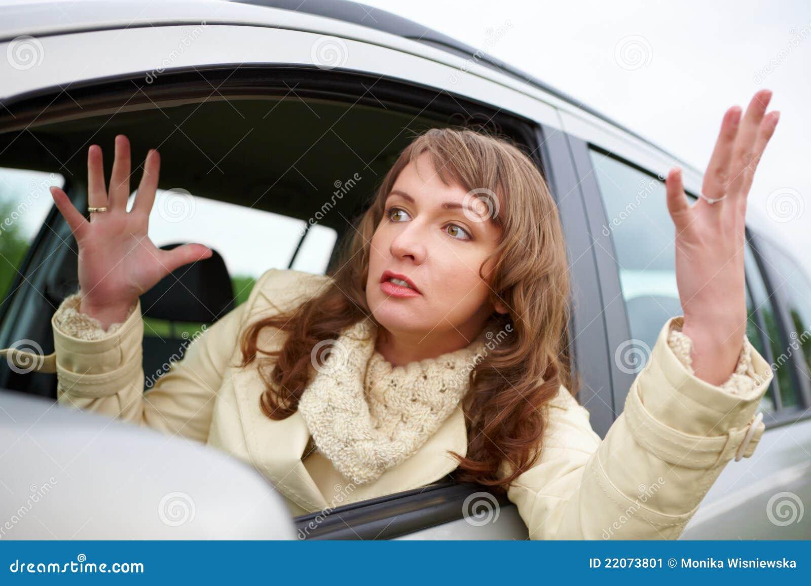 Mulher nova irritada que senta-se em um carro