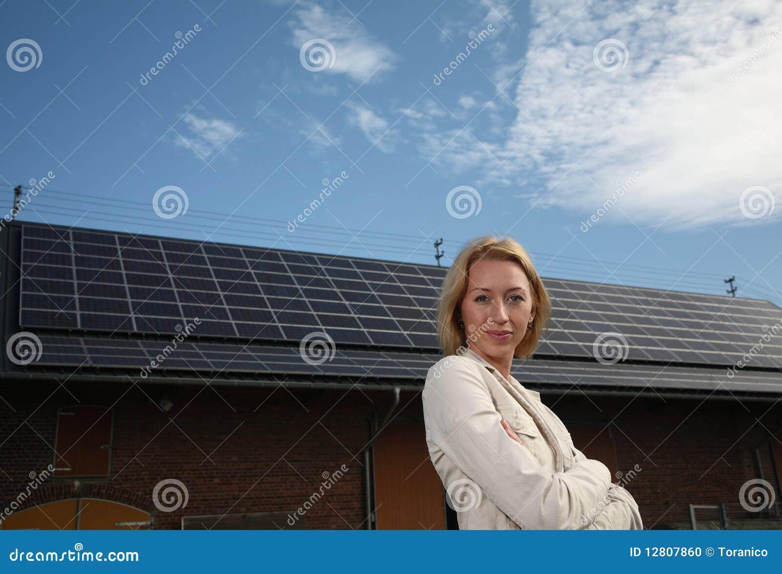 Mulher nova na frente da casa solar-psta