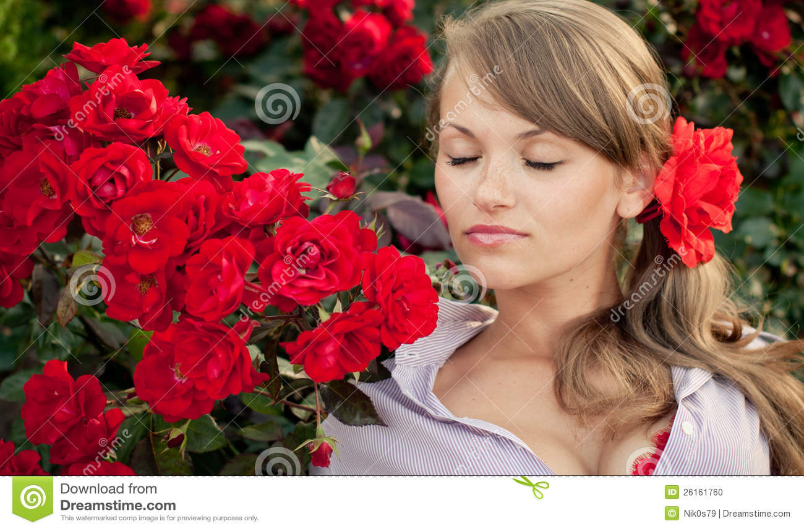 jardim rosas vermelhas:Woman Smelling Roses in a Garden