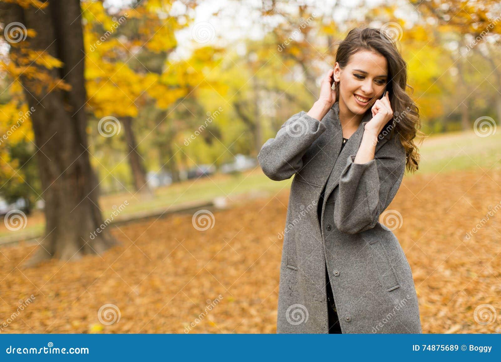 Mulher nova no parque do outono