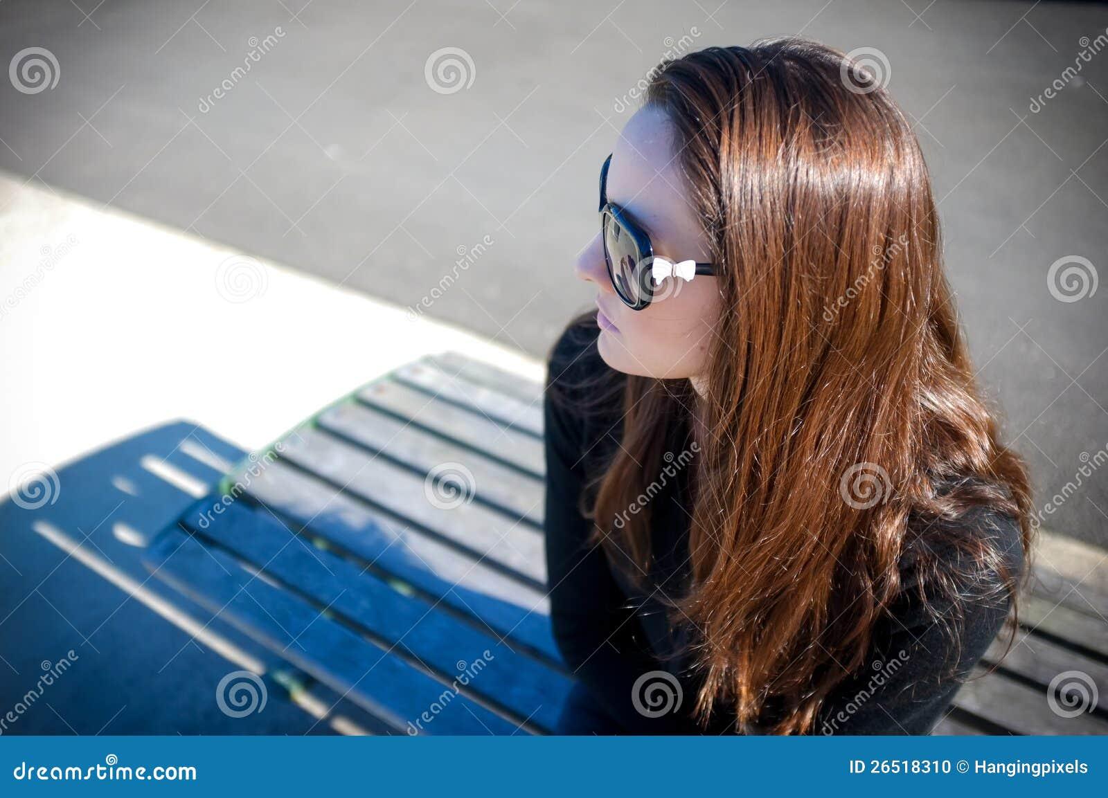 Mulher nova nos óculos de sol que sentam-se em um banco do cais