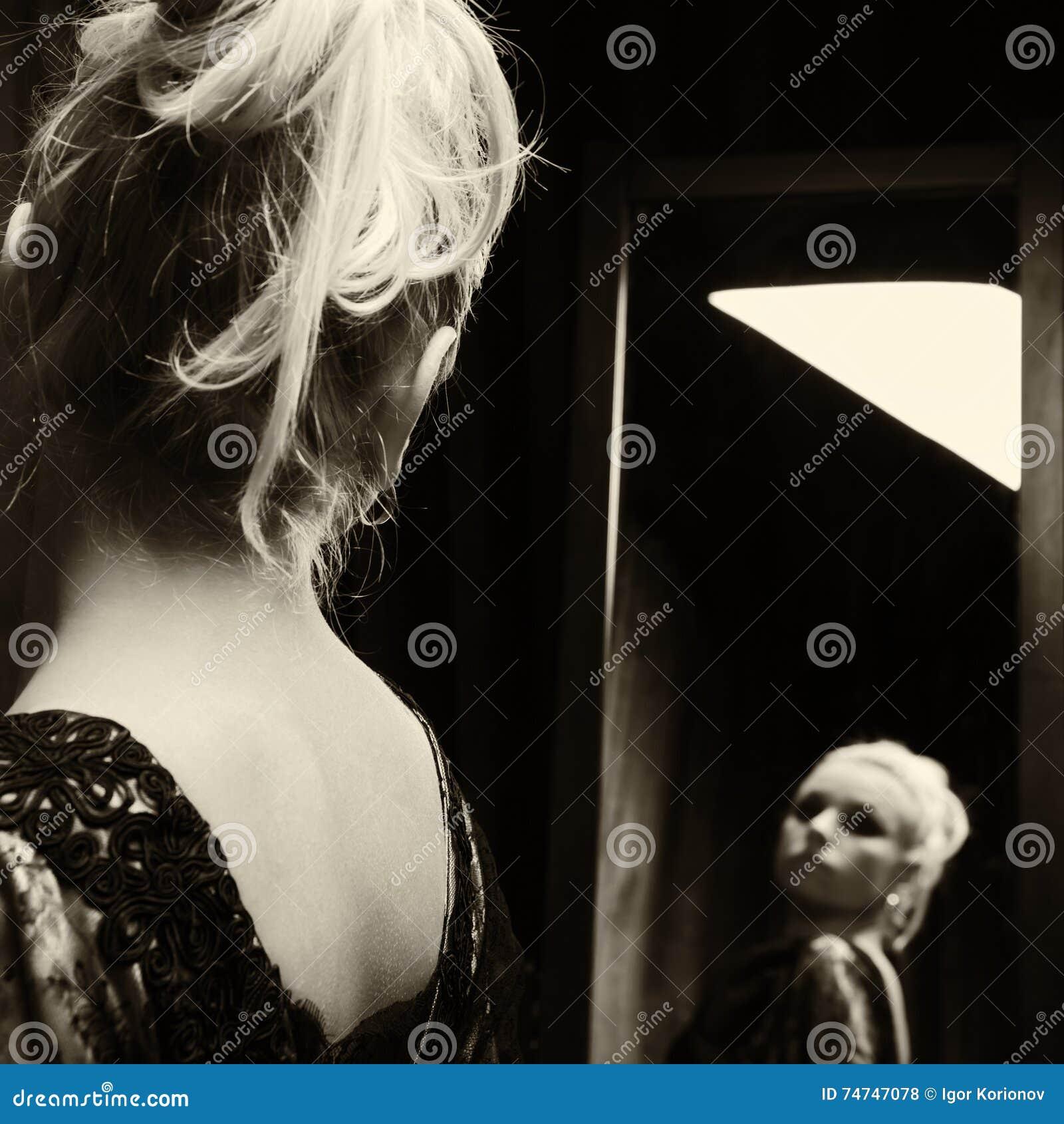 A mulher nova olha no espelho?