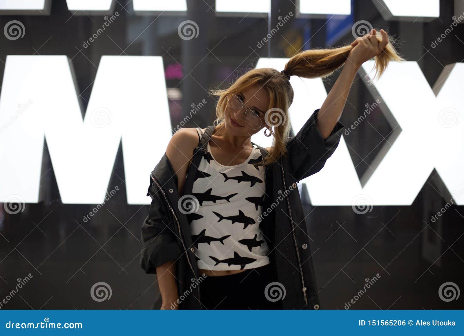 Mulher nova positiva engraçada do moderno com cabelo vermelho na roupa elegante em poses à moda dos vidros perto da parede de vid