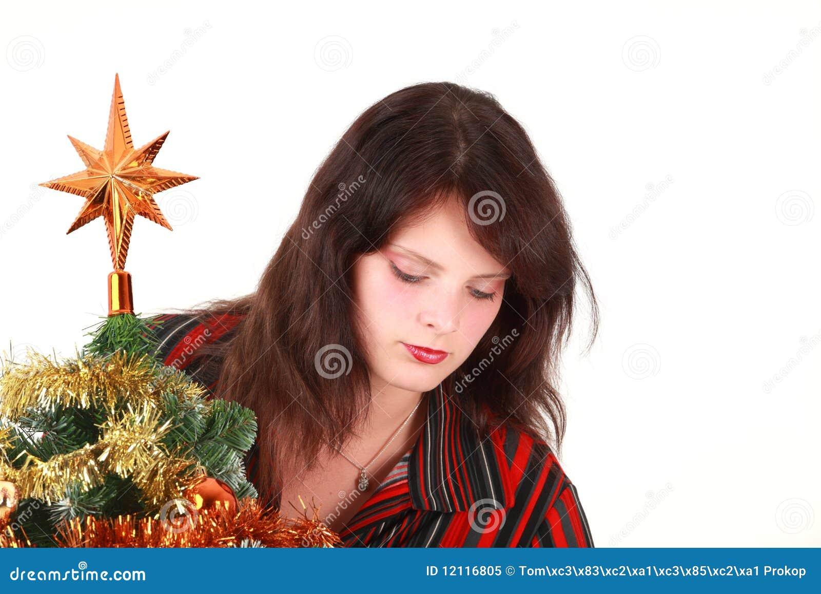 Mulher nova que decora a árvore de Natal