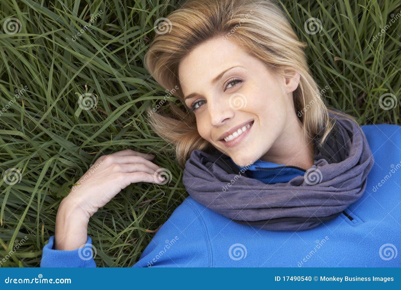 Mulher nova que encontra-se sozinho na grama