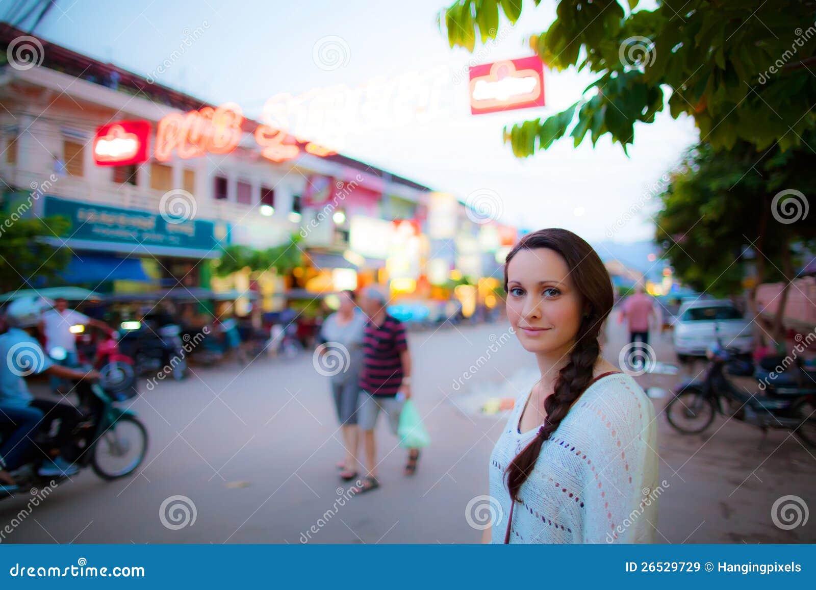 Mulher nova que espera para cruzar a estrada em Ásia