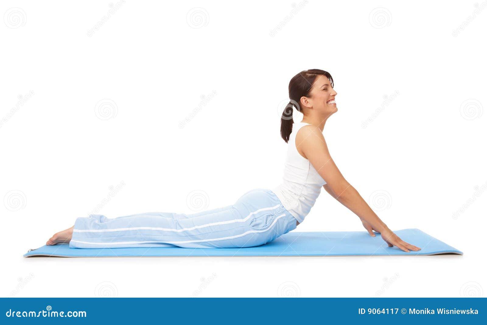 A mulher nova que fazem a ioga ou os pilates exercitam na esteira