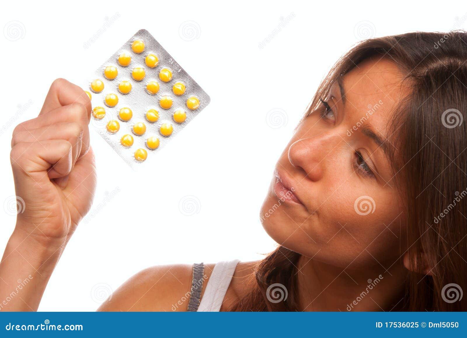 Mulher nova que olha comprimidos amarelos da tabuleta