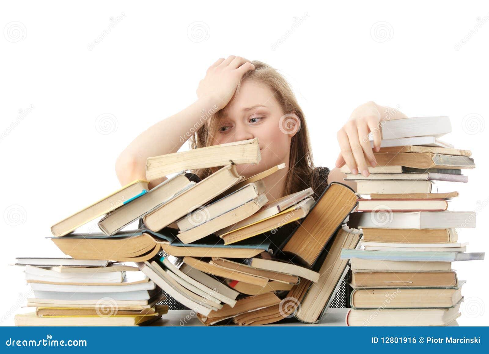 Mulher nova que senta-se atrás dos livros