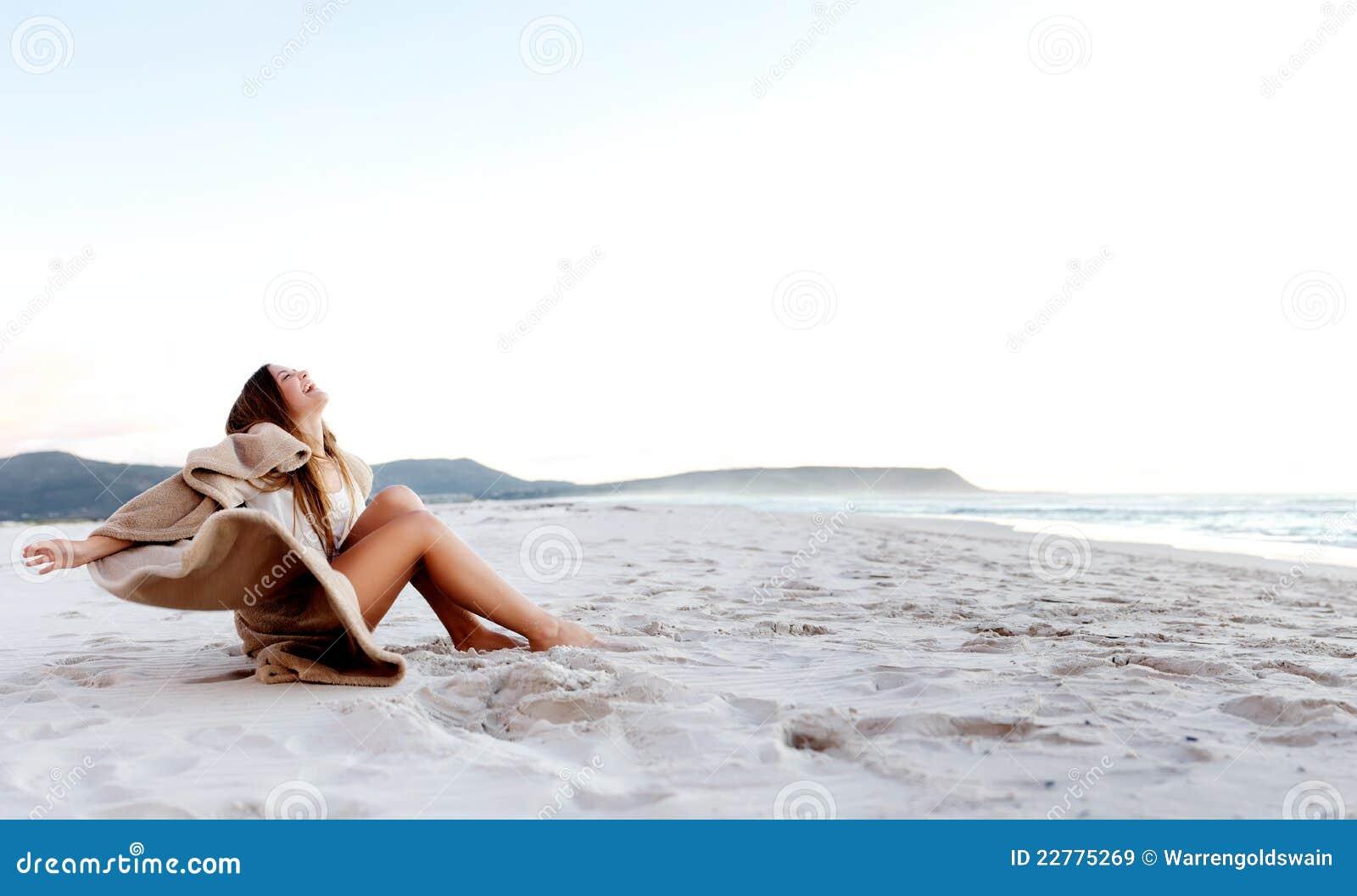 Mulher nova que senta-se na areia