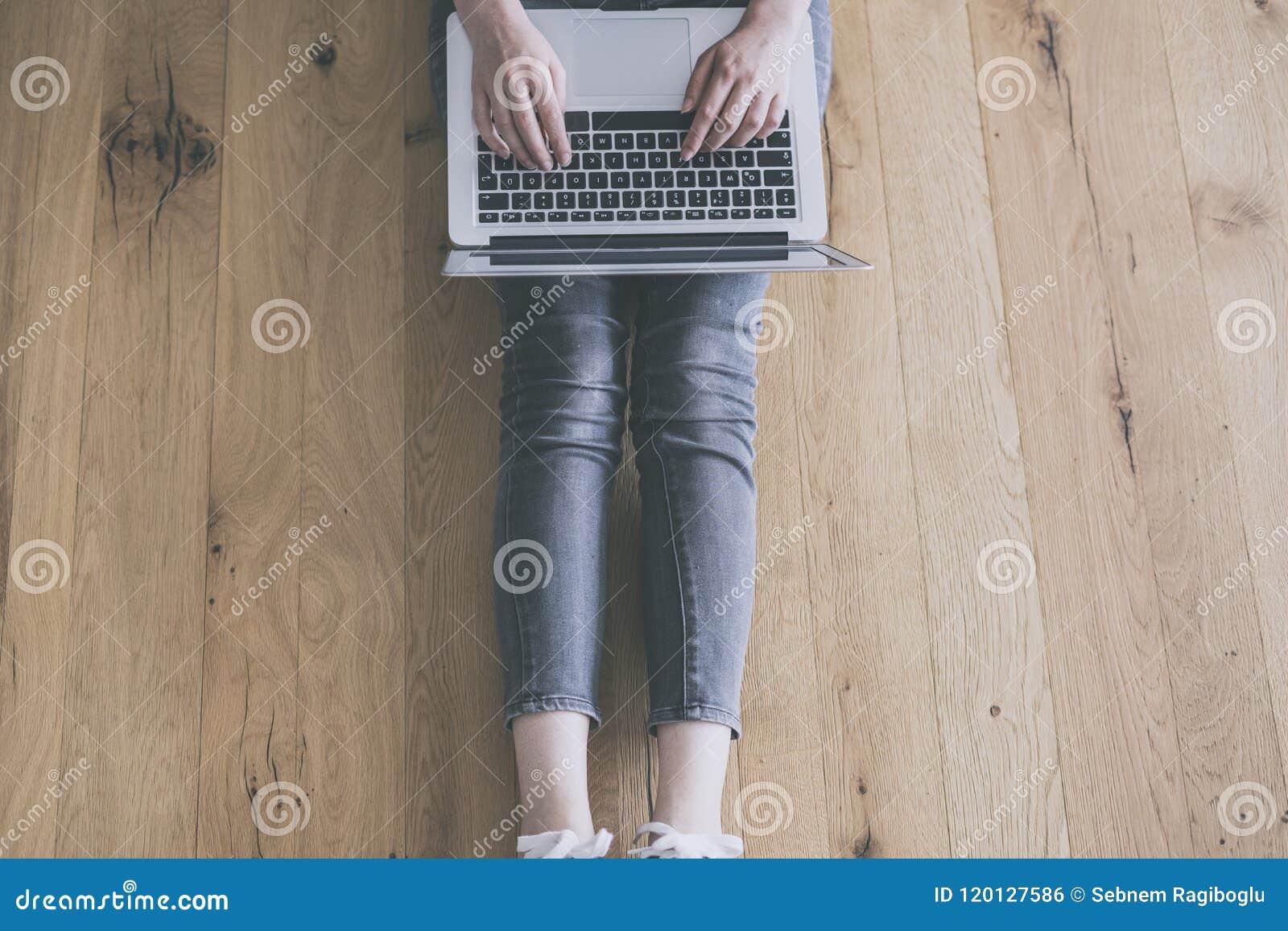 Mulher nova que trabalha no computador portátil