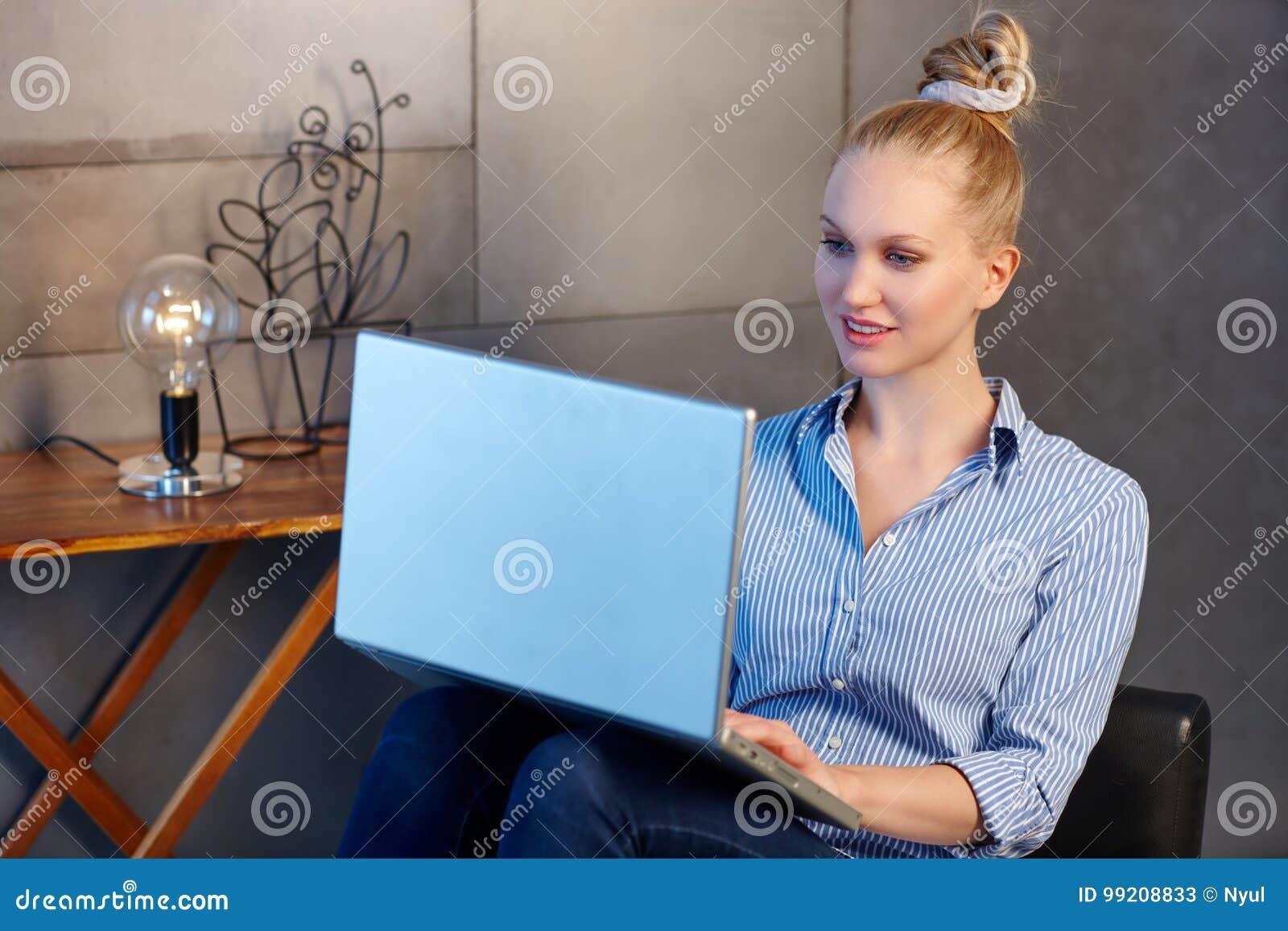 Mulher nova que usa o portátil