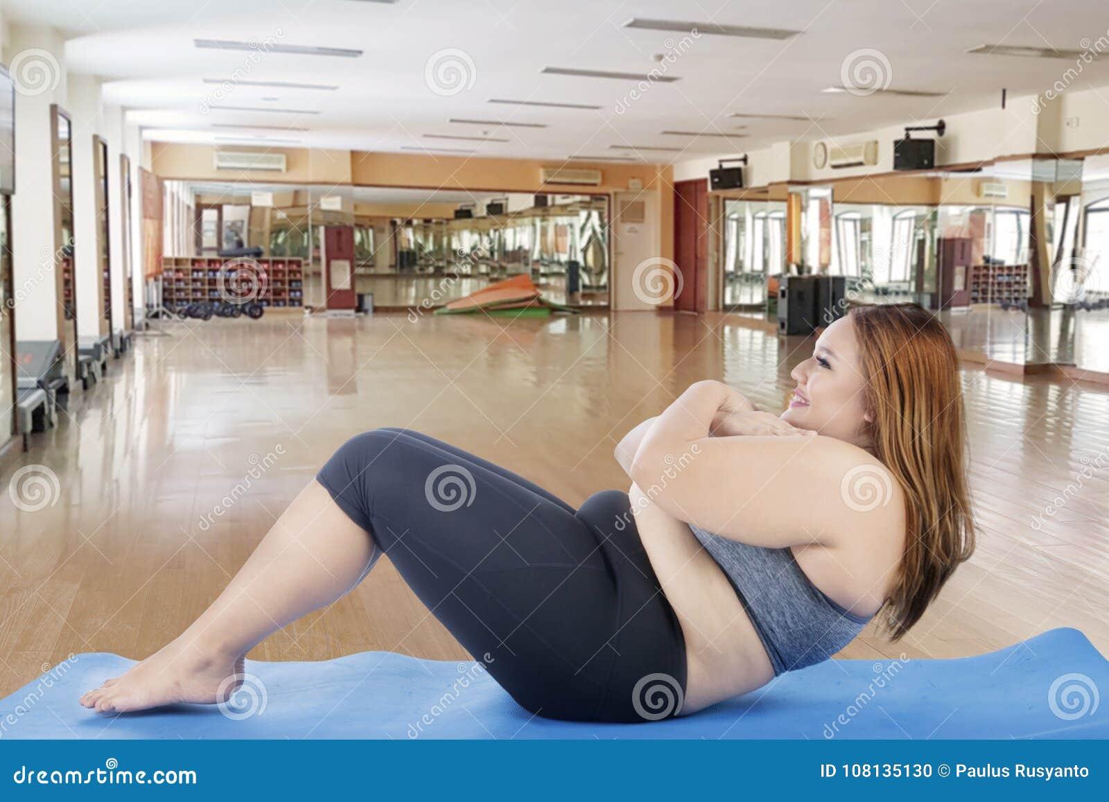 Mulher obeso que faz triturações na esteira