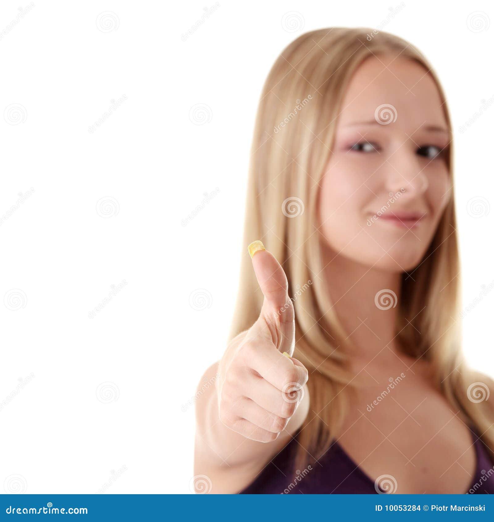 Mulher ocasional que sorri com seus polegares acima