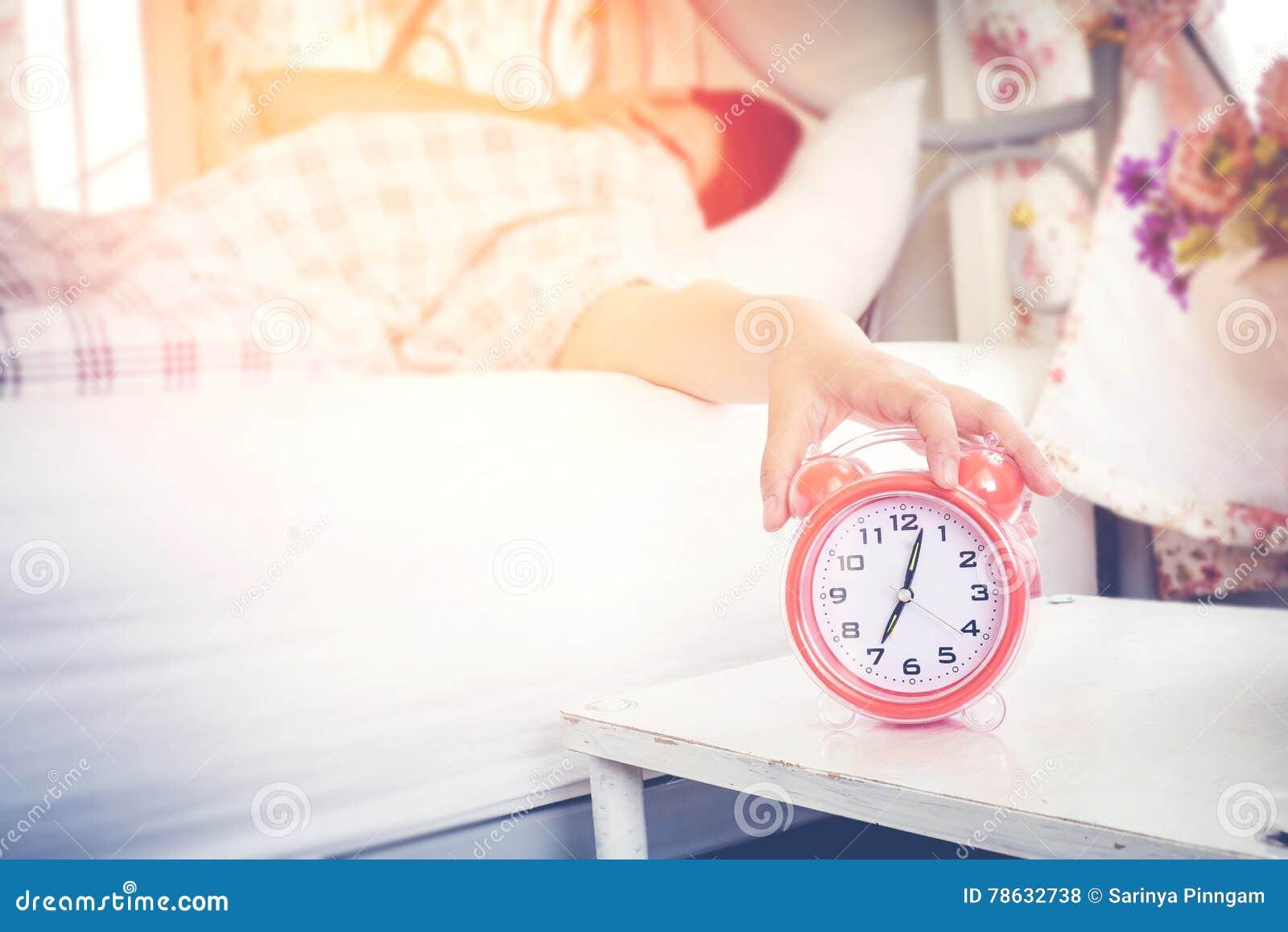A mulher odeia acordar cedo na manhã Toque sonolento da menina em