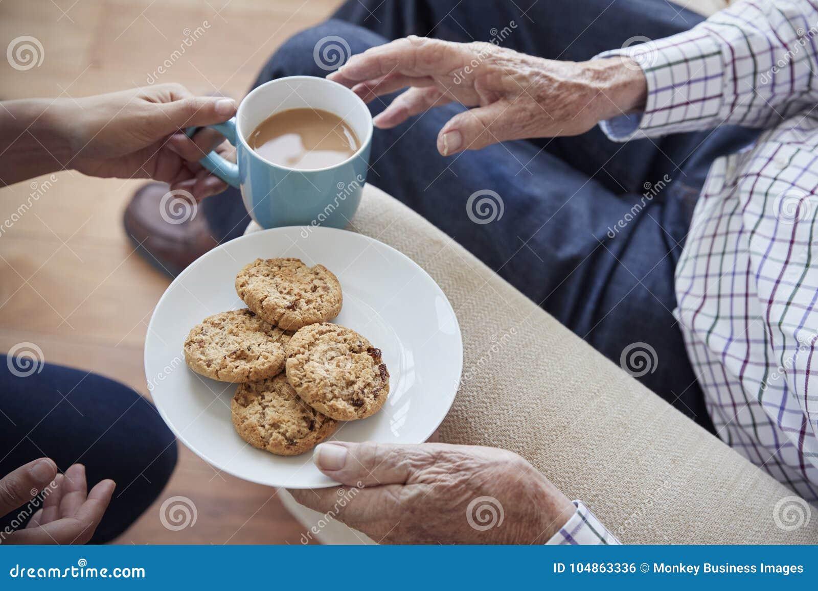 A mulher passa o chá e os biscoitos a um homem superior assentado, detalhe