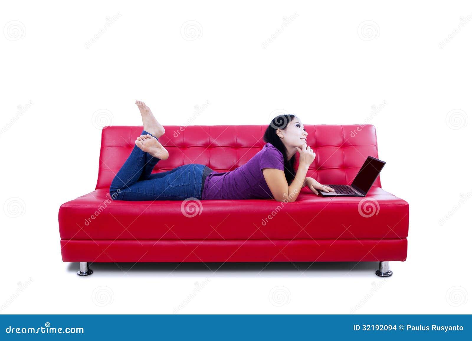 Mulher pensativa com o portátil no sofá
