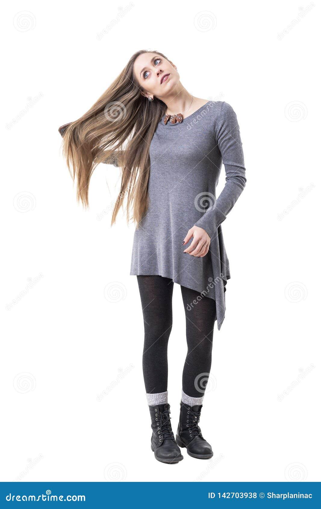 Mulher pensativa nova relaxado que olha acima sonhando acordado ao escovar seu cabelo longo