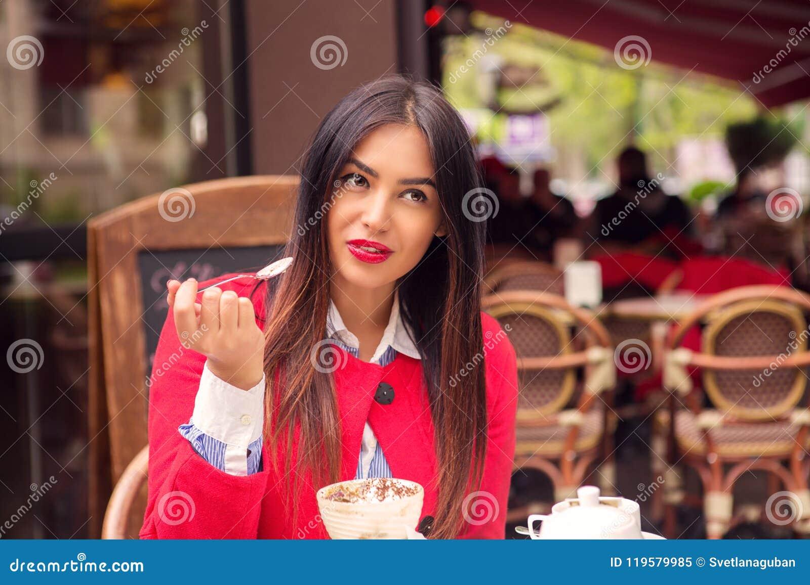 Mulher pensativa que come o deserto em um restaurante italiano