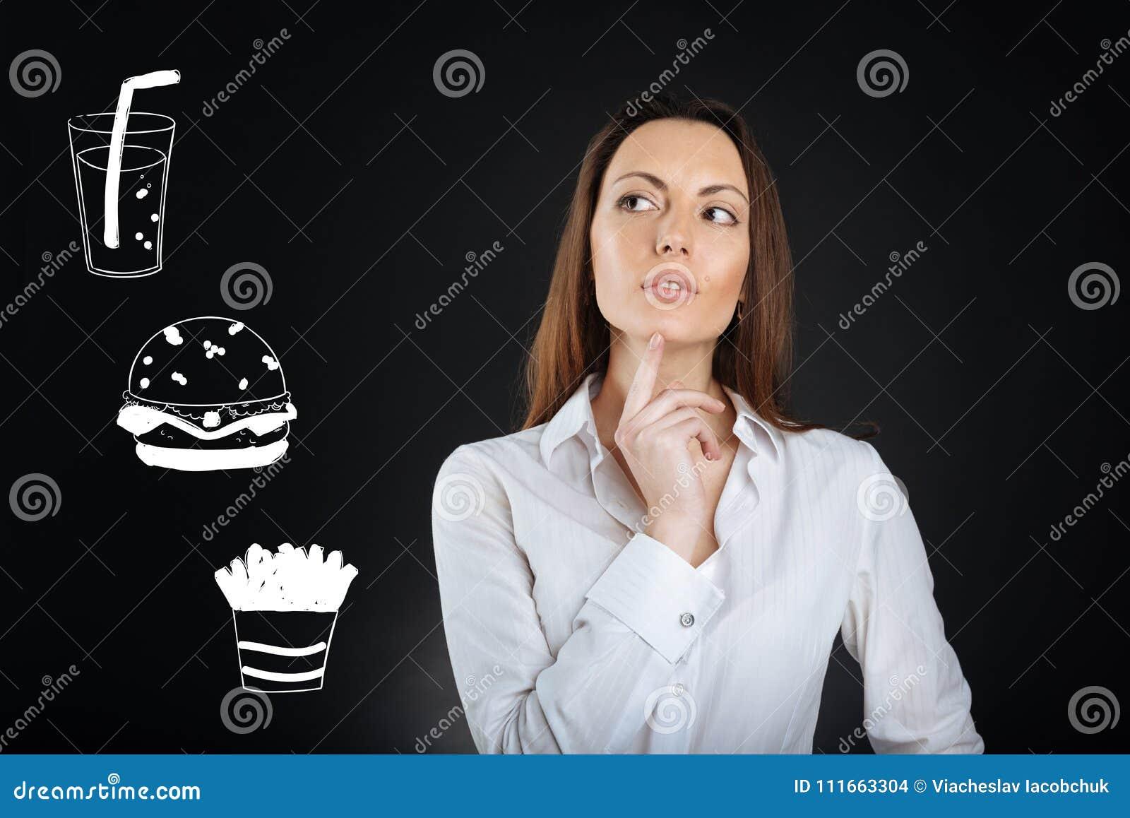 Mulher pensativa que toca em seu queixo ao escolher o alimento em um café