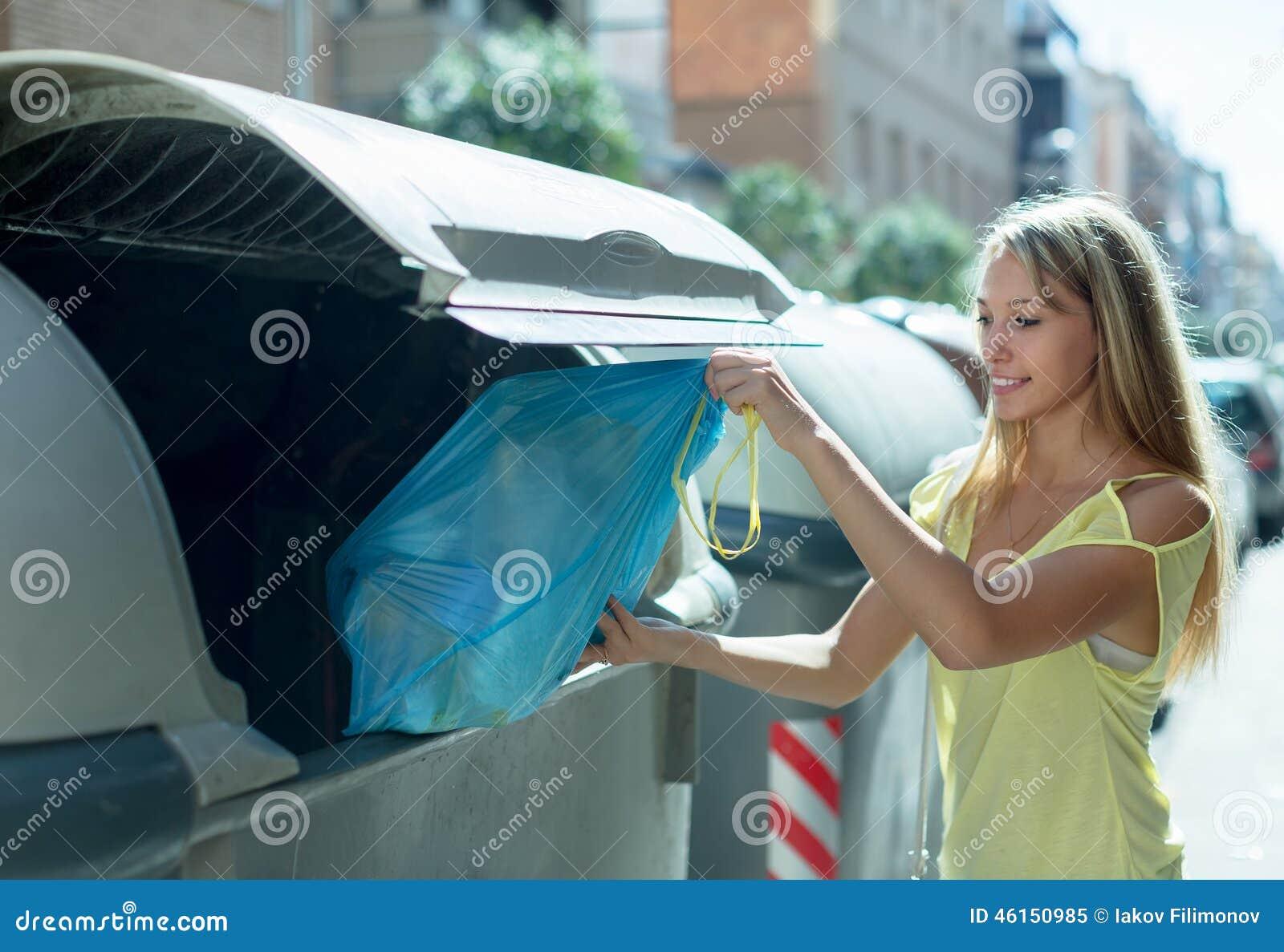 Mulher perto do escaninho de lixo