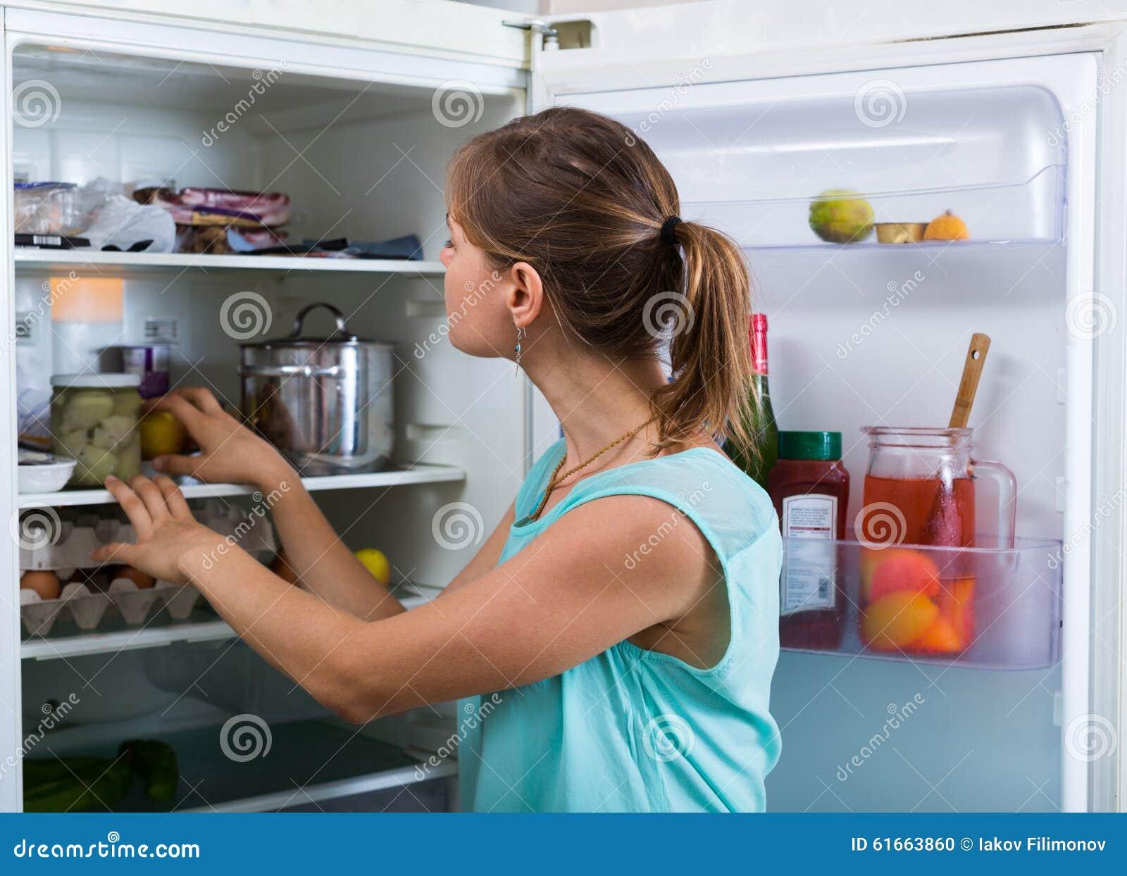 Mulher perto do refrigerador completo