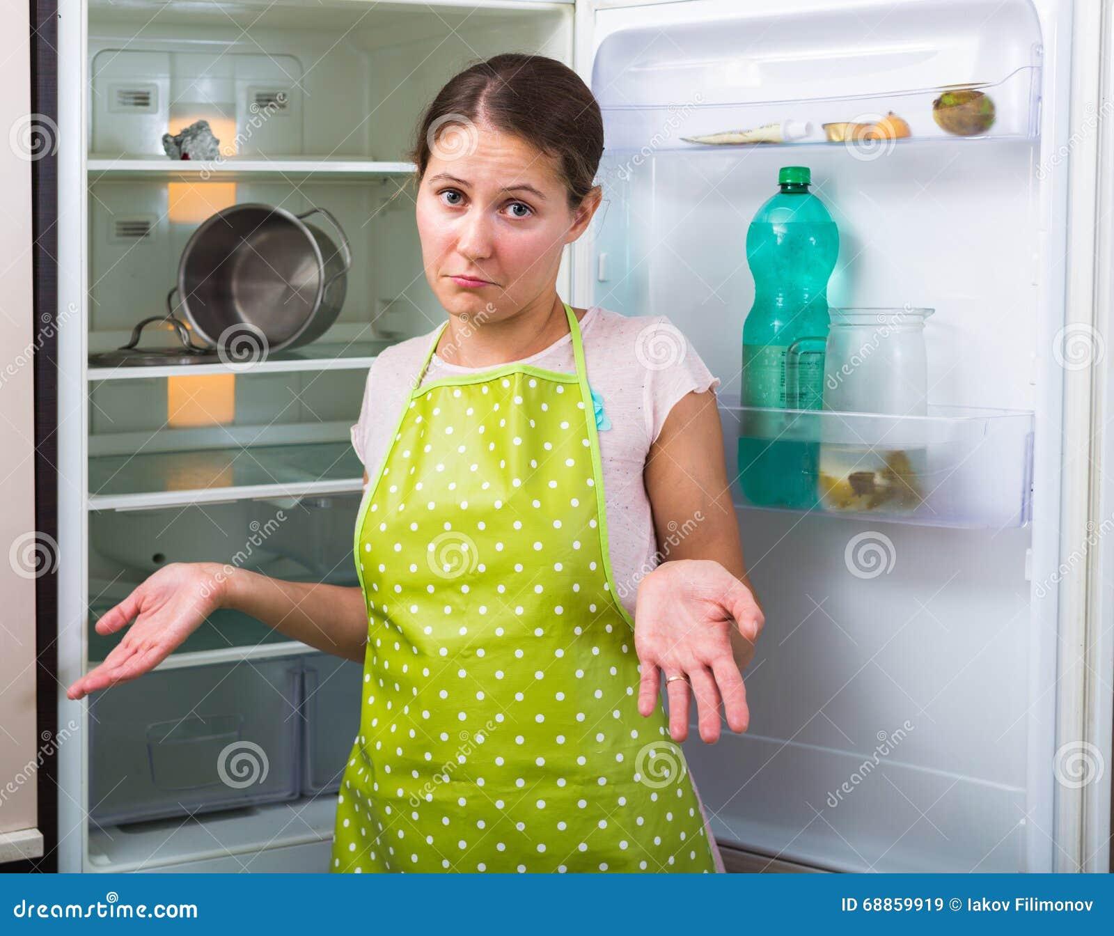 Mulher perto do refrigerador vazio