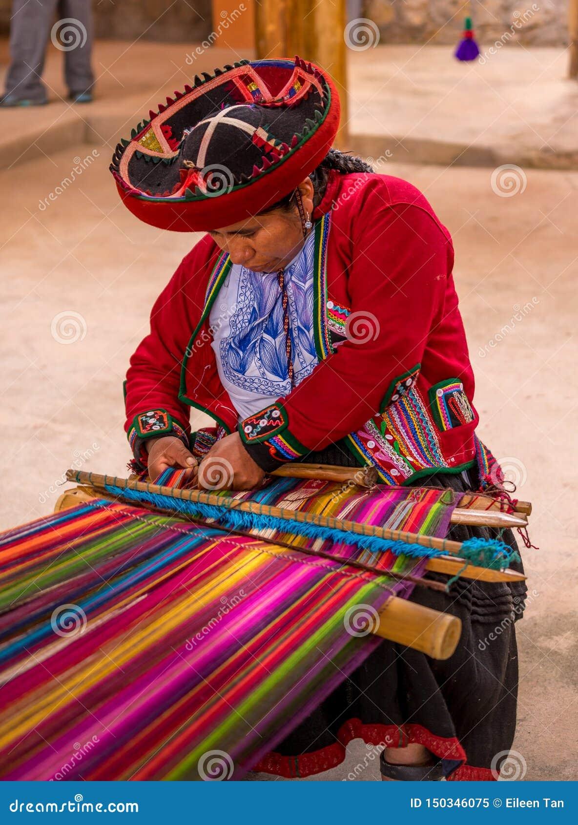 Mulher peruana que trabalha em lãs feitos a mão tradicionais