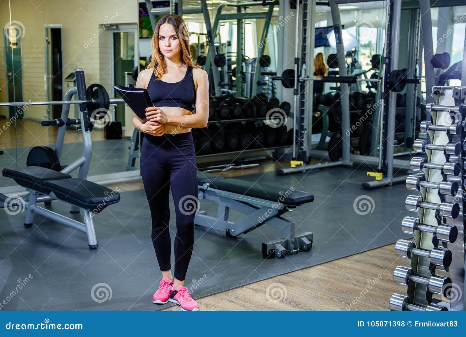 Mulher pessoal do instrutor que guarda a prancheta com plano de treinamento no gym