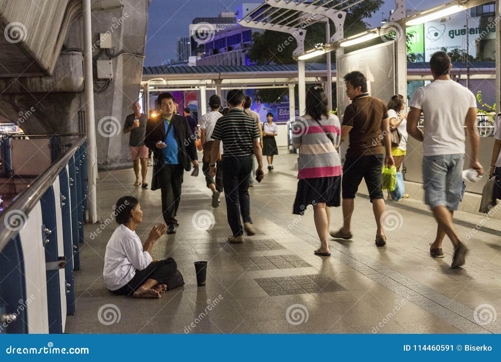 Mulher pobre que implora em Banguecoque