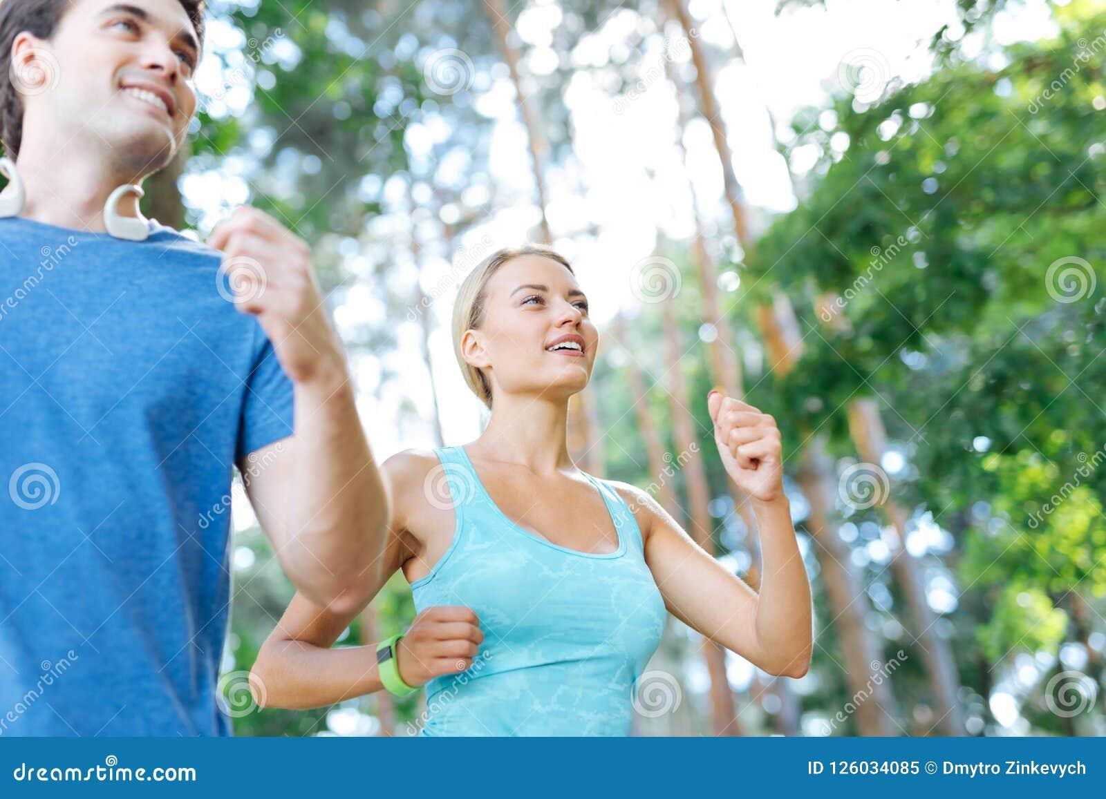 Mulher positiva alegre que aprecia sua corrida da manhã