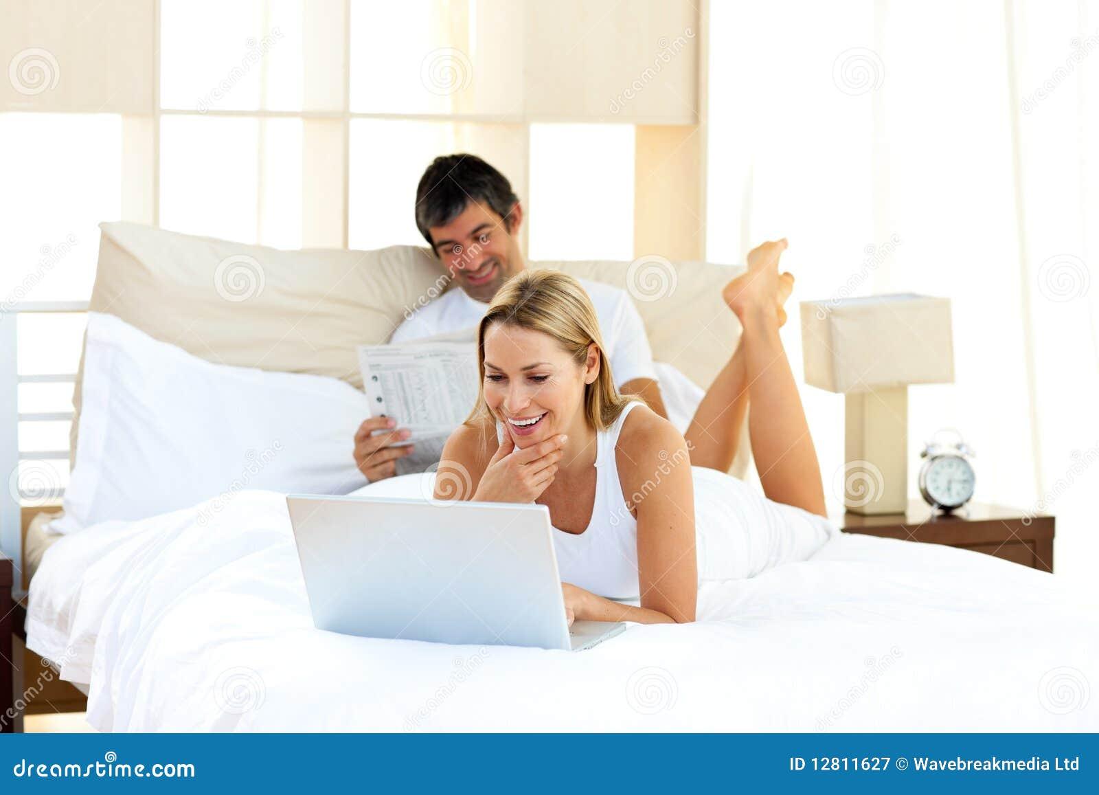 Mulher positiva que usa um portátil que encontra-se na cama