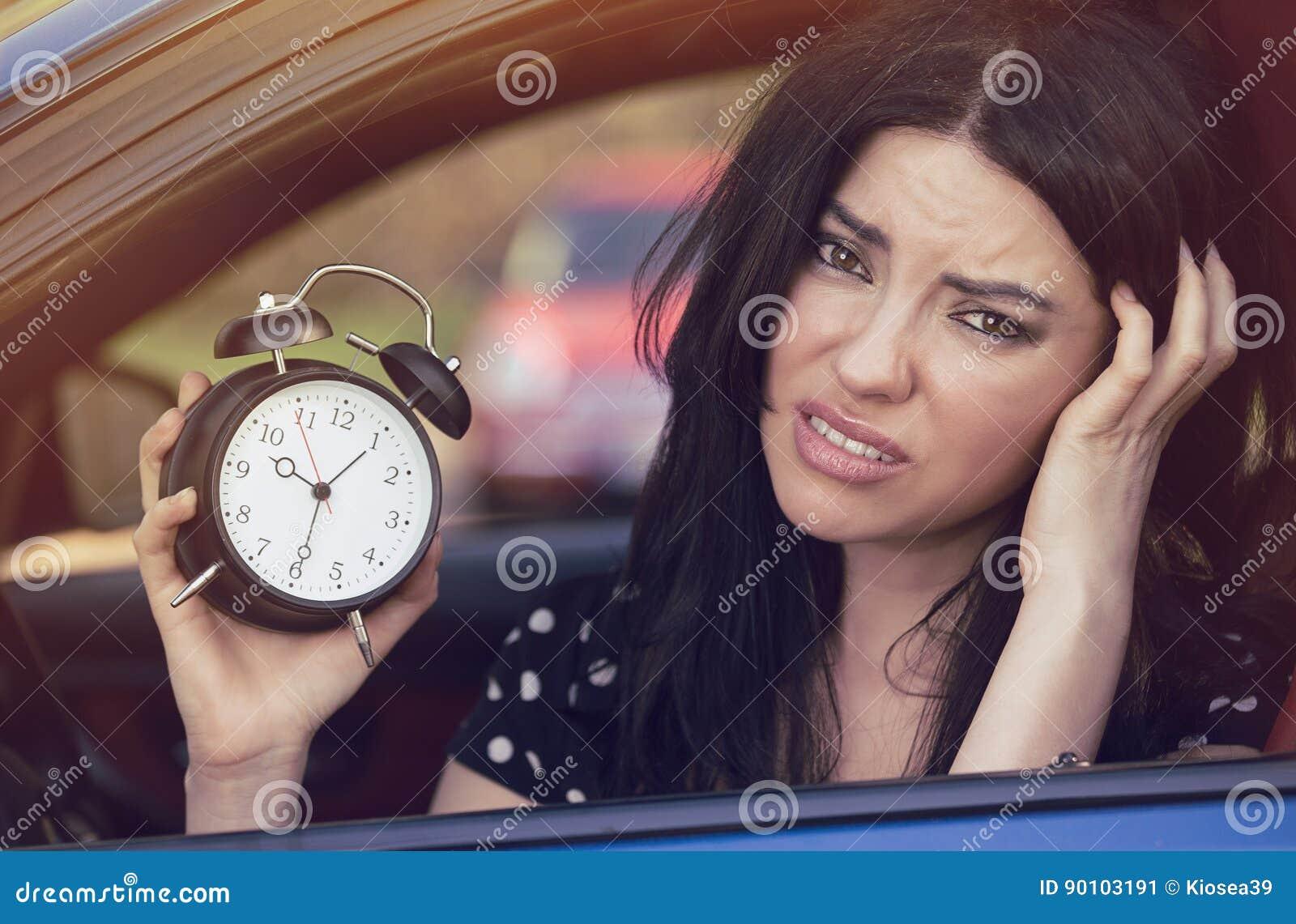 Mulher preocupada dentro do carro que mostra o despertador que corre tarde para trabalhar