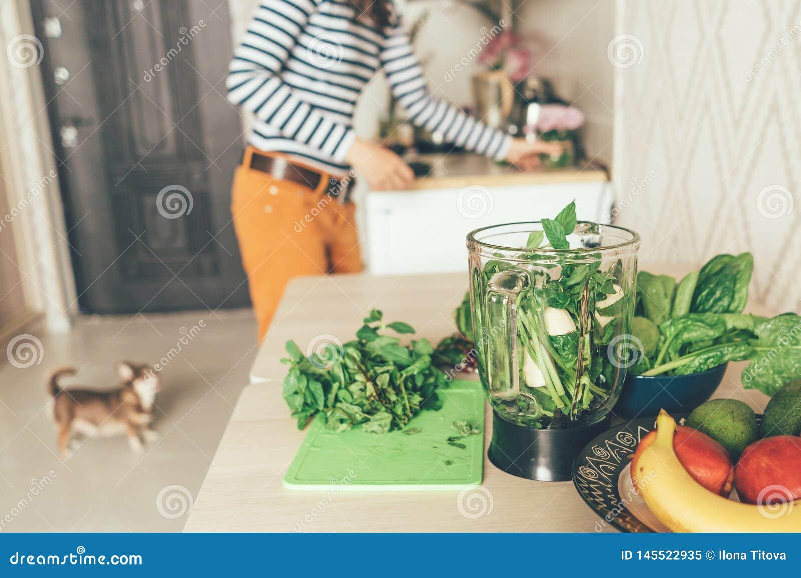 A mulher prepara produtos para um batido verde