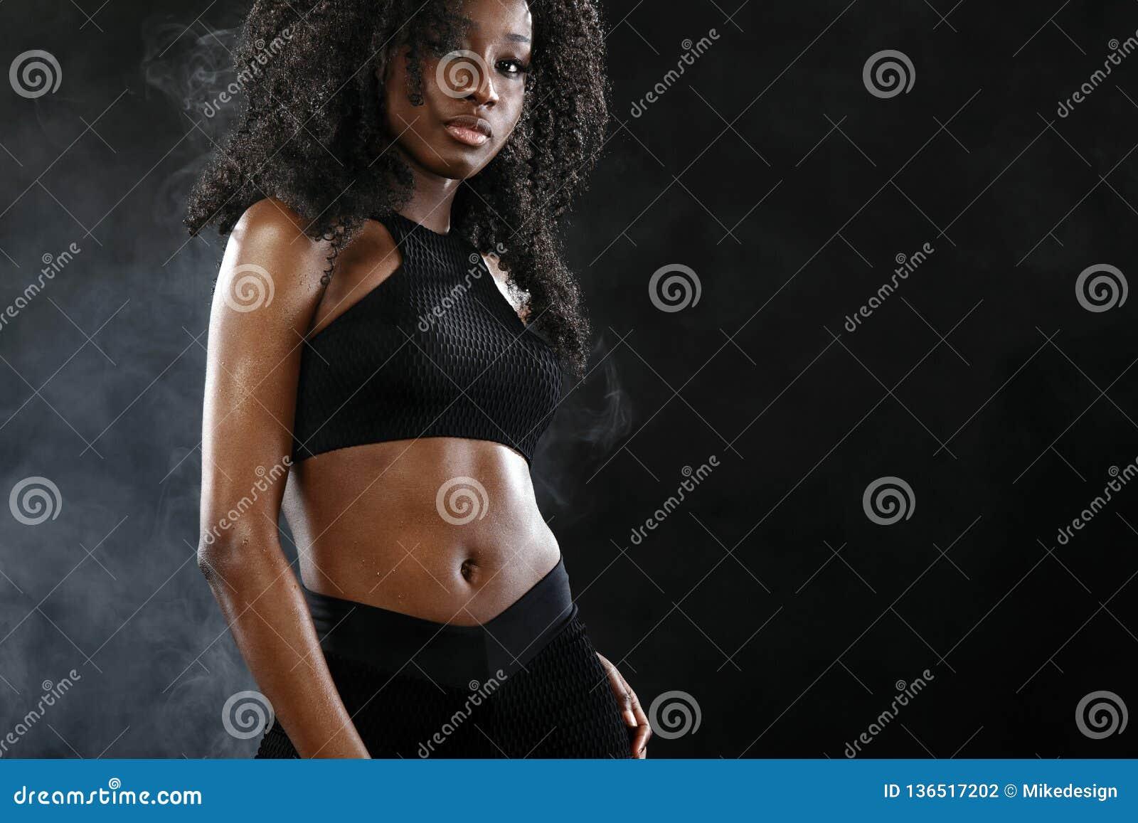 A mulher preta apta desportiva da pele, atleta faz a aptidão que exercita no fundo escuro