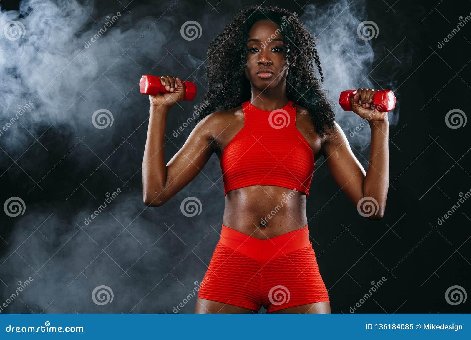 A mulher preta apta desportiva no sportswear vermelho, atleta da pele com pesos faz a aptidão que exercita no fundo escuro