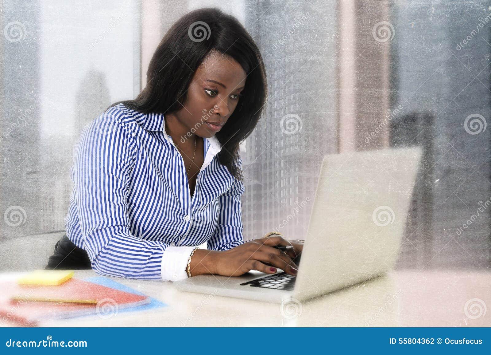 Mulher preta atrativa e eficiente nova da afiliação étnica que senta-se na datilografia da mesa do portátil do computador de escr