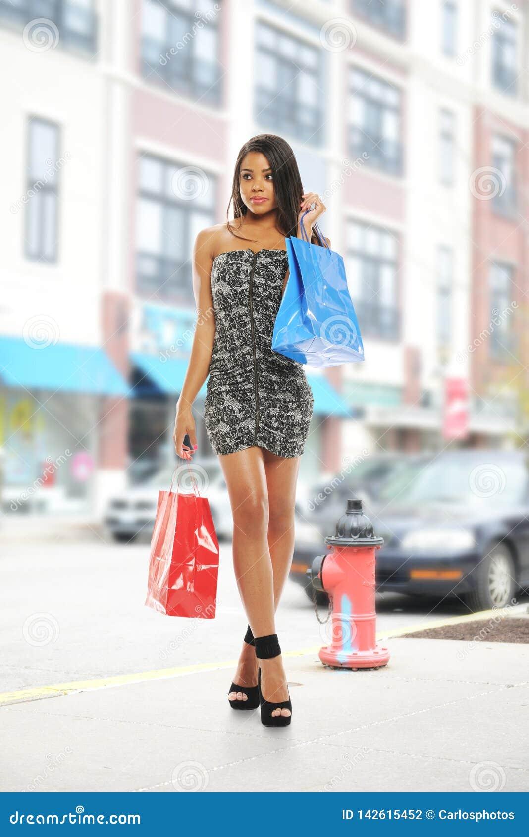 Mulher preta nova com sacos de compra