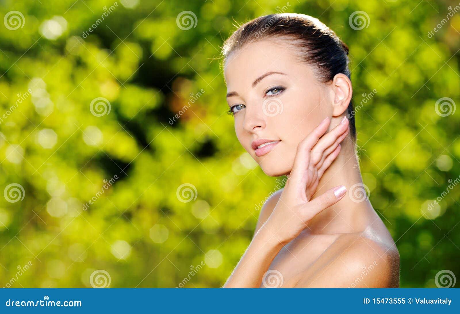 Mulher que afaga sua pele limpa fresca da face