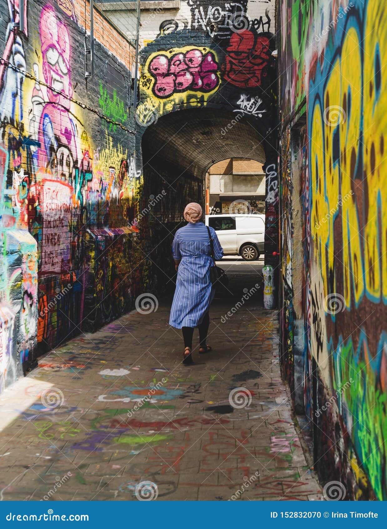 Mulher que anda abaixo da rua dos grafittis