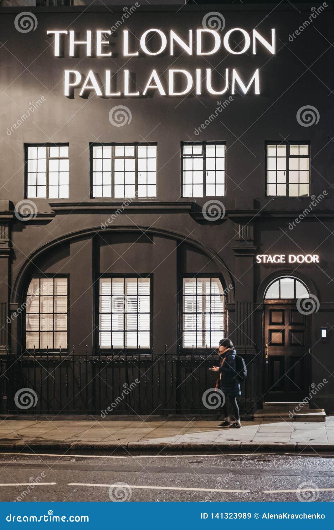 Mulher que anda após a entrada da fase ao teatro do paládio de Londres, Londres, Reino Unido