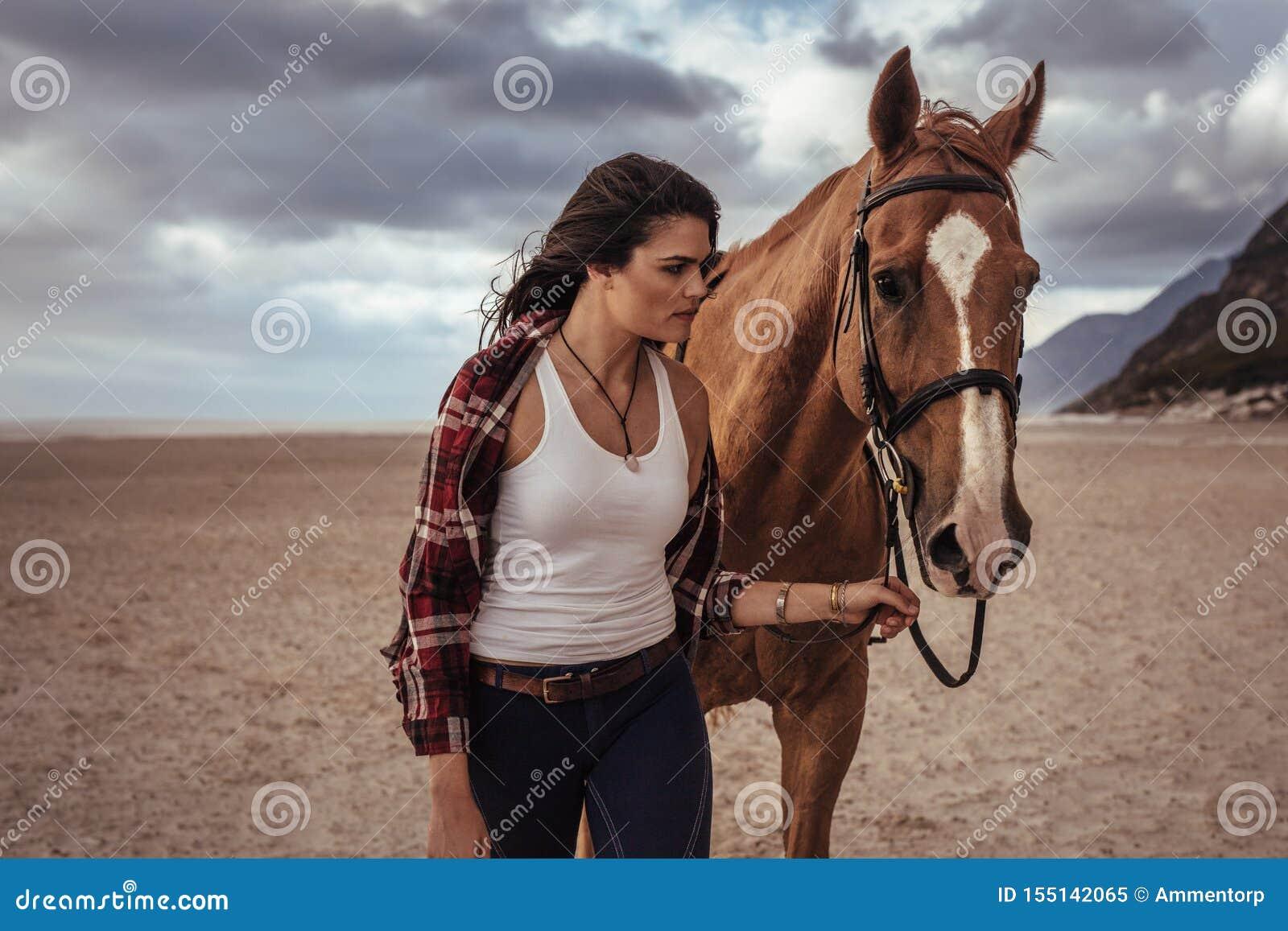 Mulher que anda com o cavalo na costa
